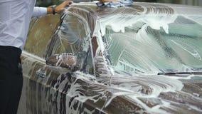 Auto que se lava de la persona con la esponja del jabón, automóvil costoso, negocio del carwash almacen de metraje de vídeo