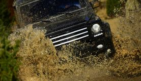 Auto racing on fall nature background. Competition, energy and motorsport concept. Off road vehicle or SUV crossing. Puddle with dirt splash. Car racing in royalty free stock images