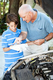 Auto Repair - Helping Dad. Father teaching his son how to check the oil on the family car royalty free stock image