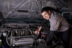 Auto Repair Mechanic. A young auto mechanic working under the hood repairing an engine