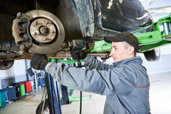 Auto repair service. Mechanic works with car suspension. Auto repair service concept. Car mechanic screwing suspension steering lever at garage shop royalty free stock photography