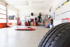 Auto Repair Shop. Defocused view into the auto repair shop with a tire in front Royalty Free Stock Photo