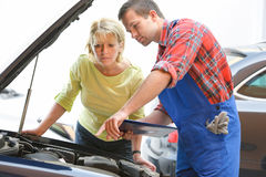 Auto repair shop. Auto mechanic and female customer in auto repair shop Royalty Free Stock Photos