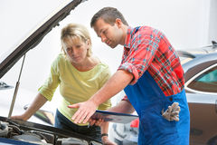 Auto repair shop. Auto mechanic and female customer in auto repair shop Stock Photography