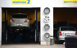 Auto Repair Shop. An auto repair shop with two garages and two cars on lifts Royalty Free Stock Photo