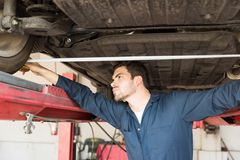 Auto Repair Shop Worker Measuring Tire Alignment With Tape. Male auto repair shop worker measuring tire alignment with tape while standing under car royalty free stock photography