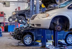 Auto repair shop working on vehicles. And fixing brakes on one of them royalty free stock photos
