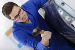 Auto repair worker flatten metal body car using hammer Stock Photos
