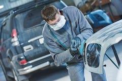 Auto repairman grinding autobody bonnet. Auto body repairs. Repairman mechanic worker grinding automobile car bonnet by grinder in garage workshop. Toned Stock Photo