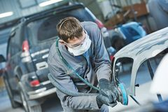 Auto repairman grinding autobody bonnet. Auto body repairs. Repairman mechanic worker grinding automobile car bonnet by grinder in garage workshop. Toned Royalty Free Stock Image