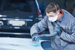 Auto repairman grinding autobody bonnet. Auto body repairs. Repairman mechanic worker grinding automobile car bonnet by grinder in garage workshop. Toned Stock Image