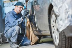 Auto repairman grinding autobody bonnet. Auto body repairs. Repairman mechanic worker grinding automobile car bonnet by grinder in garage workshop. Toned Stock Image