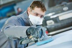 Auto repairman grinding autobody bonnet Royalty Free Stock Image