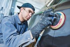 Auto repairman grinding autobody bonnet Royalty Free Stock Photography