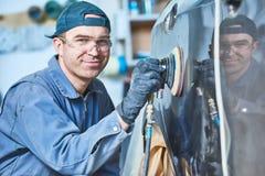 Auto repairman grinding autobody bonnet Royalty Free Stock Images