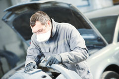 Auto repairman grinding autobody bonnet. Auto body repairs. Repairman mechanic worker grinding automobile car bonnet by sand paper in garage workshop Royalty Free Stock Images