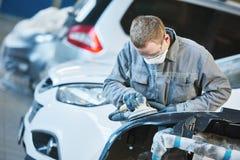 Auto repairman grinding autobody bonnet Stock Image
