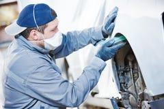 Auto repairman grinding autobody bonnet. Auto body repairs. Repairman mechanic worker grinding and sanding automobile car bonnet by grinder in garage workshop Stock Photo