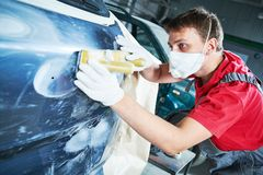 Auto repairman grinding automobile body. Auto body repairs. Repairman mechanic worker grinding automobile car body in garage workshop royalty free stock images