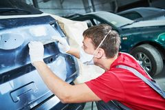 Auto repairman grinding automobile body Royalty Free Stock Image