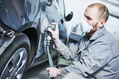 Auto repairman grinding automobile car body Royalty Free Stock Photos