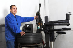 Auto repairman loading automobile car wheel at tyre fitting machine Royalty Free Stock Photo