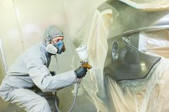 Repairman painter in chamber painting automobile car bonnet Royalty Free Stock Photo