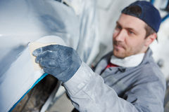Auto repairman plastering autobody bonnet. Auto body repairs. Repairman mechanic worker plastering automobile car body by plaster in garage workshop Stock Image
