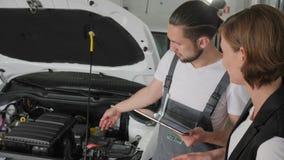 Auto repairman Pokazuje na awaria pojazdzie, auto mechanik radzi klienta, kobieta samochód łamający, usługowa pracownik rozmowa z zbiory