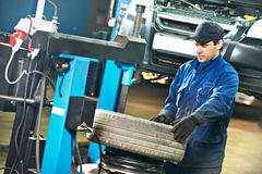 Auto repairman at tyre replacement place. Auto mechanic repairman at car tyre replacement and balancing adjustment using special equipment Stock Images
