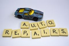 Auto repairs lettering with wreck of a toy car royalty free stock photo