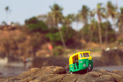 Auto rickshaw driving past palm tree forest in India. Public transport model in natural landscape of Asia Stock Image