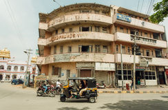 Auto-rickshaw and other vehicles driving past old hotel house on indian street Royalty Free Stock Image