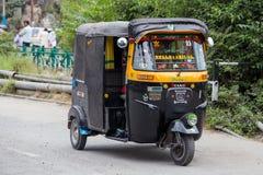 Auto rickshaw taxi on a road in Srinagar, Kashmir, India. SRINAGAR, INDIA - JULE 02, 2015: Auto rickshaw taxis on a road in Kashmir, India. These iconic taxis Royalty Free Stock Photos