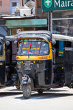 Auto rickshaw taxi on a road in Srinagar, Kashmir, India. SRINAGAR, INDIA - JULE 03, 2015: Auto rickshaw taxis on a road in Kashmir, India. These iconic taxis Royalty Free Stock Photos