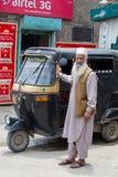 Auto rickshaw taxis and muslim man on a road in Srinagar, Kashmir. India Stock Photography