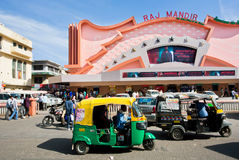 Auto rickshaw transport drive past movie theater. JAIPUR, INDIA: Auto rickshaw transport drive past the famous Raj Mandir movie theater. Raj Mandir Cinema was Stock Photography