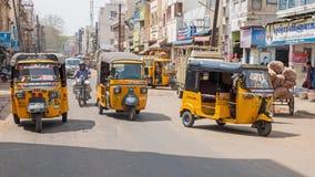 Auto rickshaws dominating traffic in Madurai. Madurai, India - March 9, 2018: Auto rickshaws dominating the roadspace in the city center. 'Tuk tuk' stock image