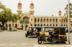 Auto-rickshaws driving past structures of the public institutions in traditional indian architecture style. MYSORE, INDIA - FEB 20: Auto-rickshaws driving past Stock Photography