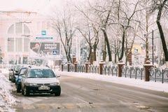 Auto's die in de weg van Overwinning in Gomel parkeren Sneeuwstraat binnen Royalty-vrije Stock Foto