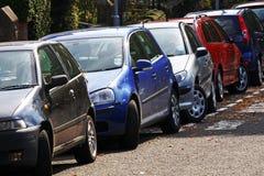 Auto's die in een stedelijke straat worden geparkeerd stock afbeelding