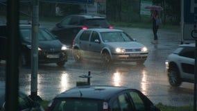 Auto's die met lichten in de regen lopen stock footage