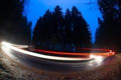 Auto's die snel door een kromme op een bosweg gaan Stock Foto