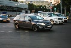 Auto's die zich bij de kruising bewegen Stock Fotografie