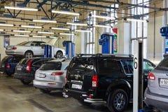 Auto's en heftoestellen in workshop van Benzinestation Stock Foto