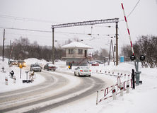 Auto's het drijven op een de winterweg over de spoorwegovergang Stock Foto