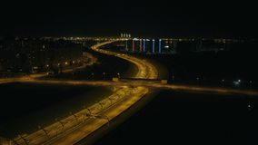 Auto's het drijven op nachtbrug over stedelijke weg in moderne stads luchtmening stock video