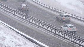 Auto's het drijven op sneeuwweg in de winter, verkeer op weg in sneeuwval, blizzard stock footage