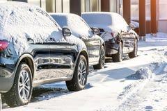 Auto's in het parkeerterrein met sneeuw wordt behandeld die stock foto's