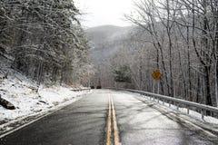 Auto's op afdaling op de sneeuwweg van het bergasfalt met twee stegen stock fotografie